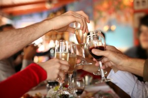 People Toasting With Wine and Champagne: Holiday Hearty Syndrome
